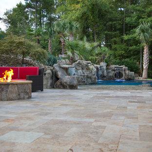 Foto de piscina con tobogán actual, grande, a medida, en patio trasero, con adoquines de piedra natural