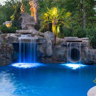 Foto de piscina con fuente exótica, grande, a medida, en patio trasero, con adoquines de piedra natural