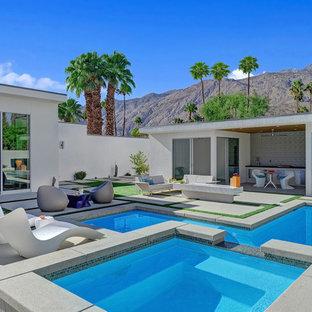 Modelo de piscinas y jacuzzis alargados, modernos, de tamaño medio, rectangulares, en patio trasero, con adoquines de hormigón