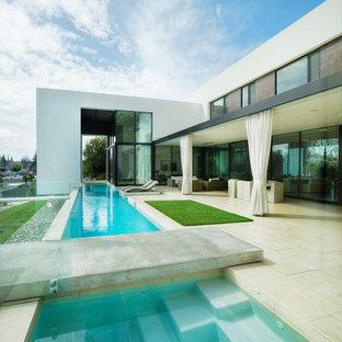Ejemplo de piscinas y jacuzzis alargados, minimalistas, de tamaño medio, rectangulares, en patio trasero, con suelo de baldosas