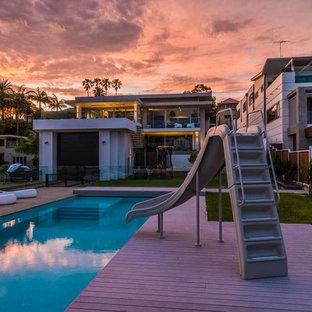 Idee per una piscina monocorsia design rettangolare di medie dimensioni e dietro casa con un acquascivolo e pedane