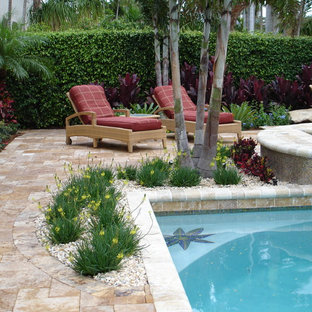 Photo of a mid-sized tropical backyard rectangular infinity pool in Miami with natural stone pavers and a hot tub.