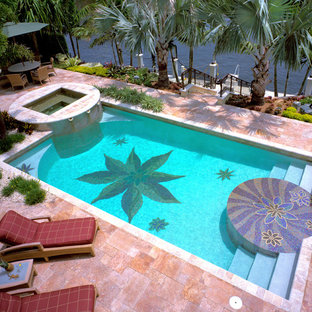 Example of a mid-sized island style backyard stone and rectangular infinity hot tub design in Miami