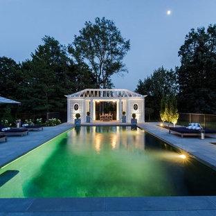 Ejemplo de casa de la piscina y piscina alargada, de estilo de casa de campo, grande, rectangular, en patio trasero, con granito descompuesto