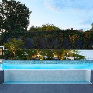 Imagen de piscina con fuente elevada, actual, a medida, en patio trasero, con adoquines de hormigón