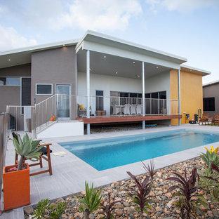 Diseño de piscina alargada, contemporánea, de tamaño medio, rectangular, en patio trasero, con suelo de baldosas