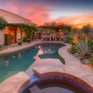 Design ideas for a mid-sized backyard custom-shaped pool in Phoenix with a hot tub and natural stone pavers.