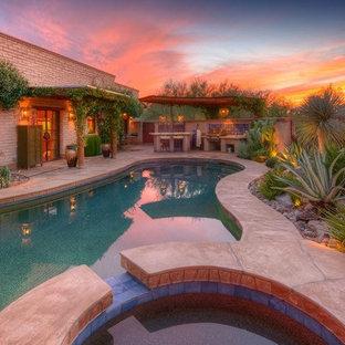 Aménagement d'une piscine arrière sud-ouest américain de taille moyenne et sur mesure avec un bain bouillonnant et des pavés en pierre naturelle.