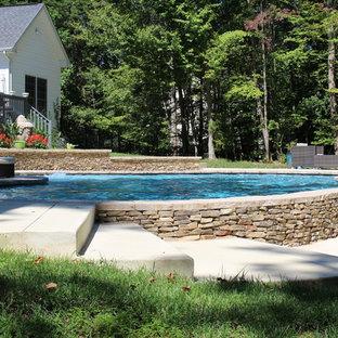 Ejemplo de piscina natural, rural, de tamaño medio, a medida, en patio delantero, con losas de hormigón