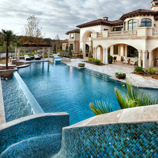 Inspiration for an expansive mediterranean backyard infinity pool in Houston with a water slide.
