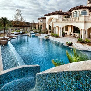 Новые идеи обустройства дома: огромный бассейн-инфинити на заднем дворе в средиземноморском стиле с водной горкой