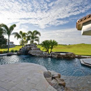 Foto de piscina con fuente alargada, tropical, de tamaño medio, en patio trasero, con adoquines de piedra natural