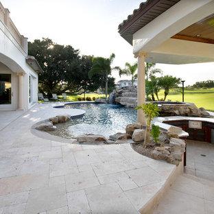 Imagen de piscina exótica, grande, a medida, en patio trasero, con adoquines de piedra natural