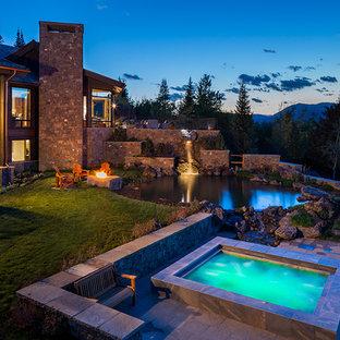 На фото: огромный естественный, круглый бассейн на заднем дворе в стиле рустика с джакузи и покрытием из каменной брусчатки