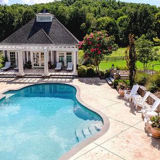 """Foto di una piscina monocorsia tradizionale a """"C"""" di medie dimensioni e dietro casa con una dépendance a bordo piscina e lastre di cemento"""