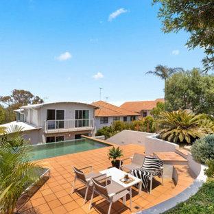 Imagen de piscina infinita, marinera, pequeña, rectangular, en patio trasero, con suelo de baldosas