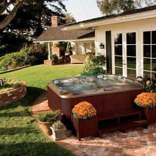 Design ideas for a small traditional backyard rectangular aboveground pool in Tampa with a hot tub and brick pavers.