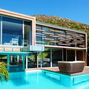 Ispirazione per una piscina fuori terra minimal rettangolare di medie dimensioni e dietro casa con una vasca idromassaggio e pedane