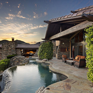 Example of a mountain style backyard stone and custom-shaped infinity pool fountain design in Phoenix