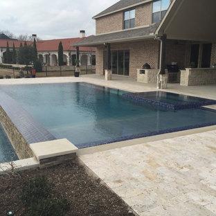 Esempio di una grande piscina a sfioro infinito minimalista rettangolare dietro casa con pavimentazioni in pietra naturale e una vasca idromassaggio