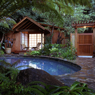 Small asian round natural pool in San Francisco with a pool house.