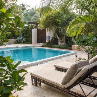 Foto de piscina tropical, rectangular, con suelo de baldosas