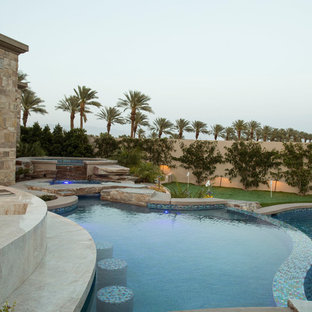 Imagen de piscina con fuente natural, tradicional renovada, de tamaño medio, redondeada, en patio trasero, con adoquines de hormigón