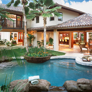 Inspiration for a large tropical backyard custom-shaped natural pool in Hawaii with a hot tub and natural stone pavers.
