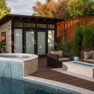 Foto de casa de la piscina y piscina actual, de tamaño medio, a medida, en patio trasero, con adoquines de piedra natural
