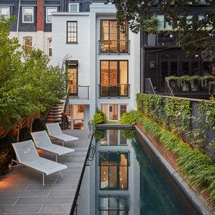 Ejemplo de piscina alargada, tradicional renovada, grande, rectangular, en patio trasero, con adoquines de piedra natural