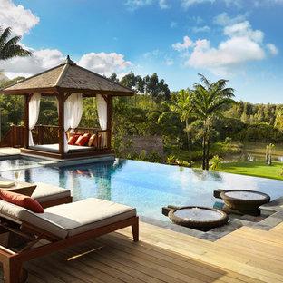 Mittelgroßer Tropenstil Infinity-Pool hinter dem Haus in rechteckiger Form mit Dielen in Hawaii