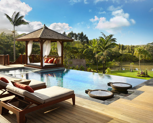 example of a mid sized island style backyard rectangular infinity pool design in hawaii with