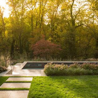 Esempio di una piscina a sfioro infinito moderna rettangolare di medie dimensioni e davanti casa con pavimentazioni in pietra naturale
