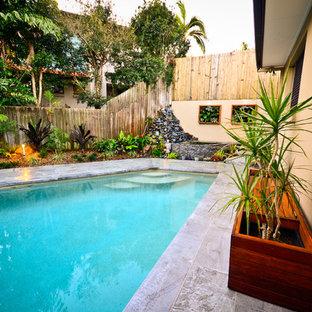 Foto de piscina alargada, asiática, de tamaño medio, a medida, en patio trasero, con adoquines de hormigón