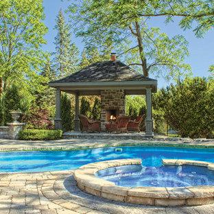Modelo de casa de la piscina y piscina natural, tradicional, grande, tipo riñón, en patio trasero, con adoquines de ladrillo