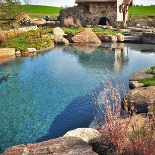 Design ideas for a large country backyard custom-shaped natural pool in Philadelphia with a pool house and natural stone pavers.