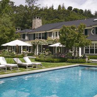 Esempio di una piscina monocorsia vittoriana rettangolare di medie dimensioni e dietro casa con una vasca idromassaggio e lastre di cemento