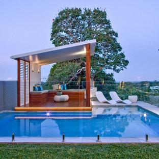 Imagen de casa de la piscina y piscina elevada, minimalista, de tamaño medio, a medida, en patio trasero, con adoquines de piedra natural