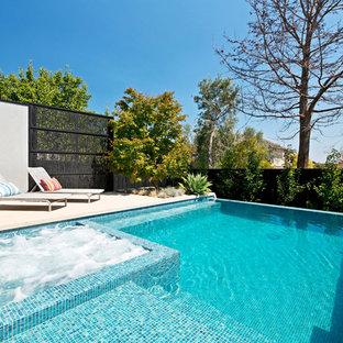 Idées déco pour une grand piscine à débordement et arrière contemporaine rectangle avec des pavés en béton.