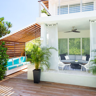Example of a mid-sized beach style backyard rectangular lap pool house design in Miami with decking