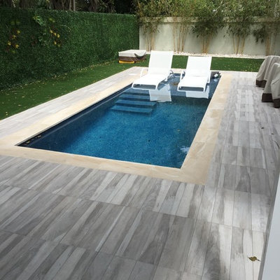 Inspiration for a small contemporary backyard rectangular and tile lap pool remodel in Miami