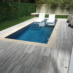 Small contemporary back rectangular lengths swimming pool in Miami with tiled flooring.