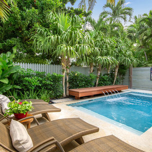 Inspiration for a tropical backyard stone and rectangular lap pool fountain remodel in Miami