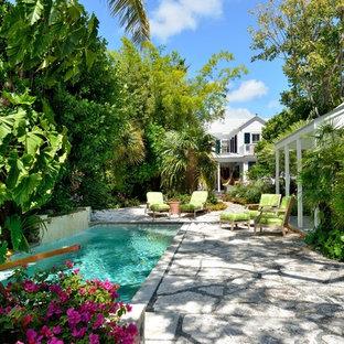 Imagen de casa de la piscina y piscina tropical, rectangular, en patio trasero, con adoquines de hormigón