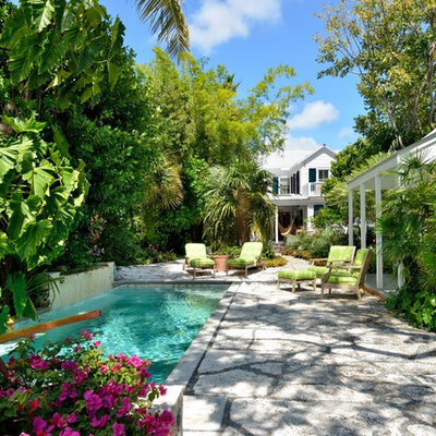 Example of an island style backyard concrete paver and rectangular pool house design in Miami