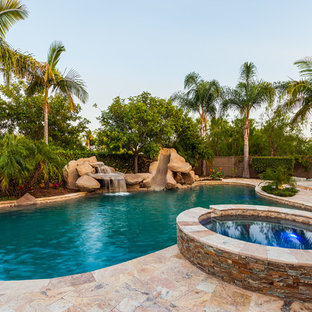 This is an example of a large tropical backyard custom-shaped pool in San Diego with natural stone pavers and a water slide.