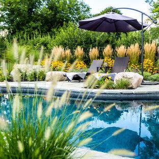 Ejemplo de piscina rural, de tamaño medio, tipo riñón, en patio trasero, con adoquines de piedra natural