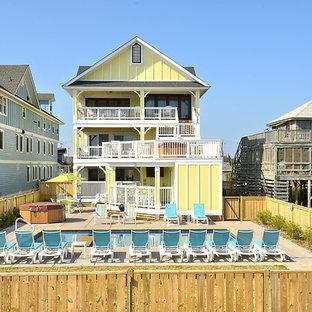 Ispirazione per una grande piscina monocorsia costiera rettangolare dietro casa con una vasca idromassaggio e pavimentazioni in cemento