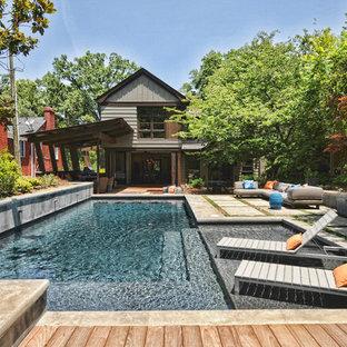 Diseño de piscina alargada, rústica, en forma de L, en patio trasero, con entablado