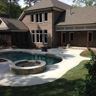 Example of a mid-sized classic backyard concrete and kidney-shaped lap hot tub design in Raleigh